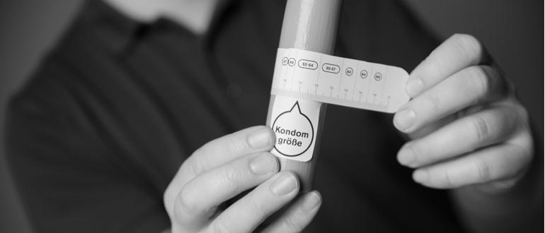 Mit einer Schere schneidest Du das Vinico-Maßband aus und wickelst dieses einmal um Deinen erigierten Penis. Dann liest Du Deine Kondomgröße ab. (Bild: © Vinico)